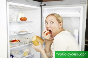 The woman greedy eats meal against an open refrigerator